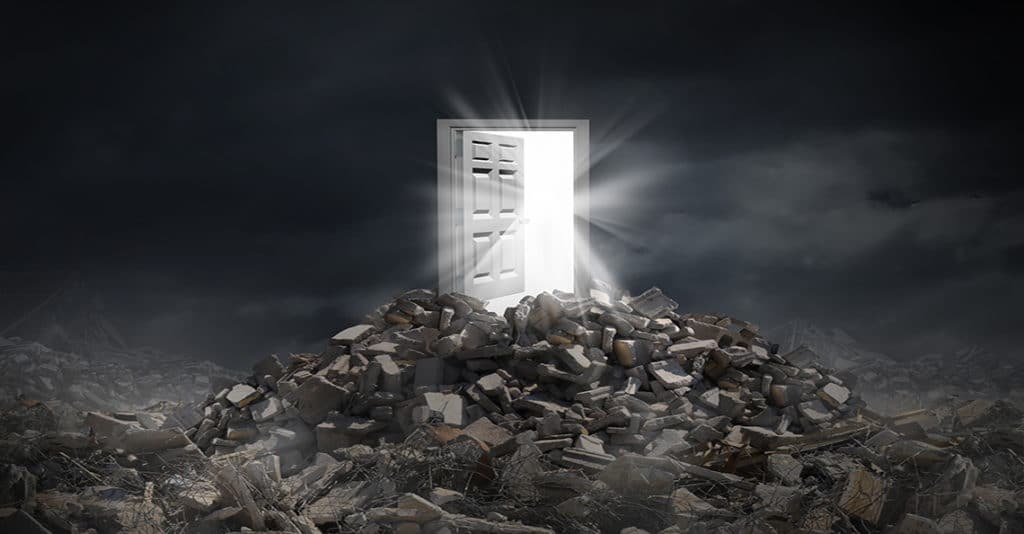 a door on top of rubble showing light at the end of the tunnel