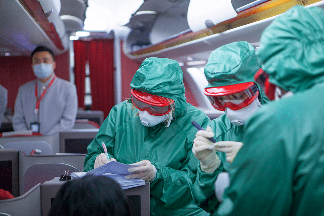 Doctors screening for coronavirus on an airplane