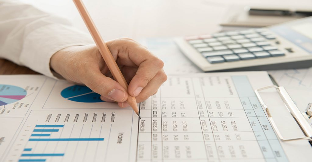 man writing on financial spreadsheets